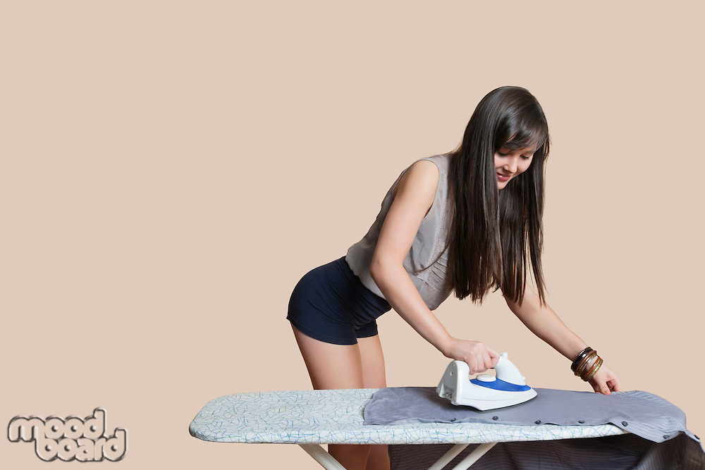 Young woman ironing shirt over colored background