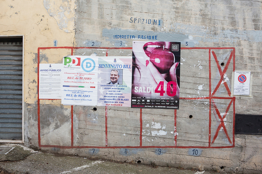 GRASSANO, ITALY - 24 JULY 2014: A poster on wall invites the citizens of Grassano to participate to the welcome ceremony for the arrival of mayor of New York Bill de Blasio in Grassano, his ancestral home town in Italy, on July 24th 2014.<br /> <br /> New York City Mayor Bill de Blasio arrived in Italy with his family Sunday morning for an 8-day summer vacation that includes meetings with government officials and sightseeing in his ancestral homeland.