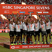 FIji celebrates its Singapore 7's Cup Championship on the victory podium after its 28-22 over Australia with time expired at the Singapore National Stadium, Singapore, Singapore.  Photo by Barry Markowitz, 4/29/18, 9pm