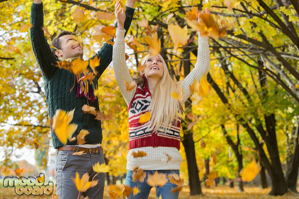 Couple enjoying falling autumn leaves in park