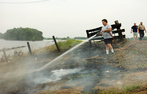 Volunteer firefighter Bill Field Jr. puts out a fire at the Highway 61 North entrance to the Backwater Levee on Tuesday afternoon. According to volunteer fire department coordinator Kelly Worthy, the fire probably started after a cigarette butt was thrown out of a passing car but was quickly put out with no damage to the levee system. (Bryant Hawkins/The Vicksburg Post)