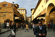 Tourists and locals shop and wonder along the Ponte Vecchio, a 13th century bridge that is famous for its jewellery shops.  Ponte Vecchio is in Florence, Italy.