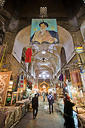 Shoppers walk through a bazaar in Isfahan, Iran, with a poster of Ayatollah Khamenei hanging above.