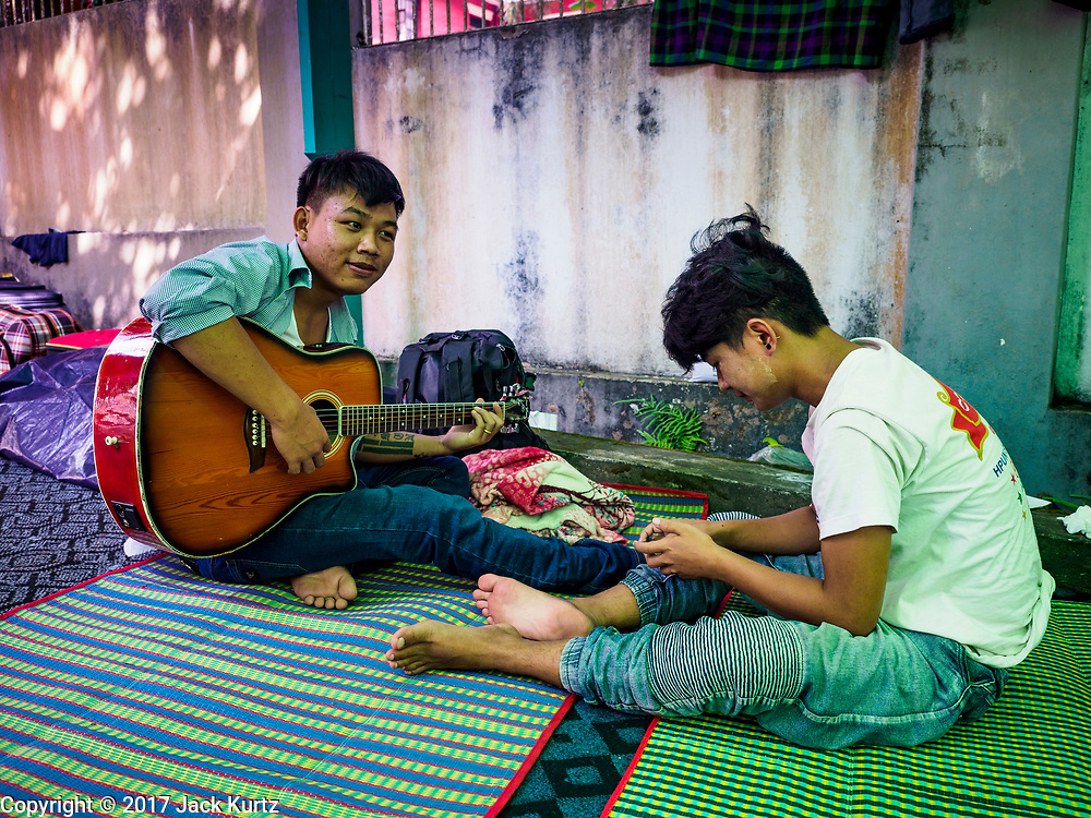 28 NOVEMBER 2017 - YANGON, MYANMAR: A teenager going to the papal mass Wednesday plays guitar while relaxing with friends at St. Francis of Assisi Church in Yangon. About 1,500 people are camping at the church before the papal mass at Kyaikkasan Sports Ground, about three kilometers from the church.    PHOTO BY JACK KURTZ