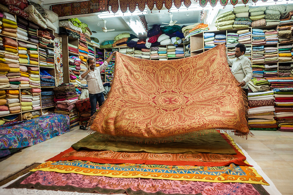 Two men in a showroom laying out different textiles / blankets for customers to see and buy, Jodhpur, Rajasthan, India.