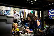 Gisele Fetterman, wife of Braddock Mayor John Fetterman, and their son August, sort shoes at the Free Store in Braddock, Pa.<br />