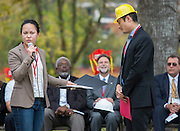 Beth Martin, left, presents a declaration from State Representative Gene Wu to Chaolin Chang, right, during a groundbreaking ceremony for the new Mandarin Chinese Language Immersion Magnet School, December 6, 2014.