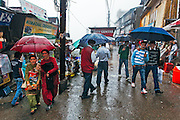 People with their umbrellas walking in the lower bazaar of Shimla in heavy rainfall.