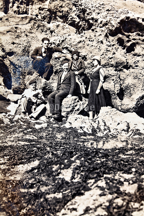 1930s group posing by a rock mountain