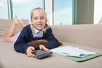 Portrait of little girl holding calculator while lying on sofa