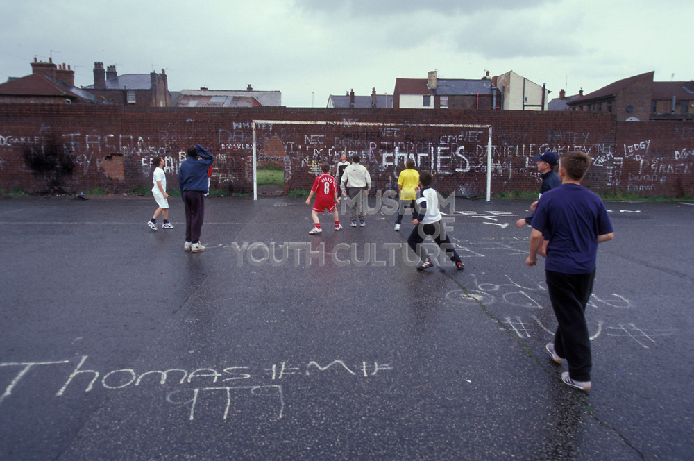 Kids playing football on a concrete football pitch, UK, 2000's