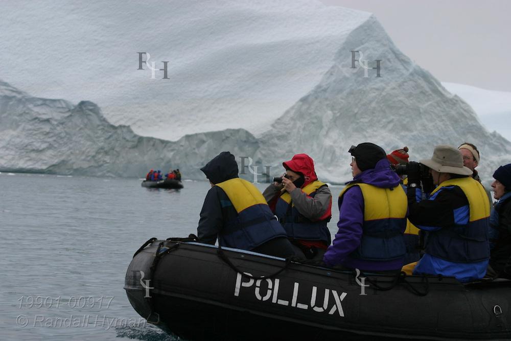 Cruise ship passengers in rubber Zodiac raft explore field of massive icebergs at Ilulissat Kangerlua Icefjord in Disko Bay, Greenland.