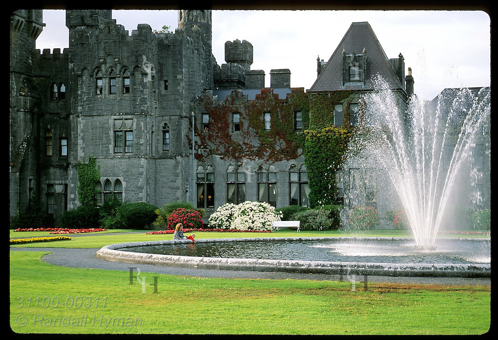 Mom & kid play at fountain behind 83-room Ashford Castle, one of Ireland's finest hotels; Cong. Ireland