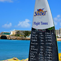 Flight Times at Maho Beach near Phillipsburg, Sint Maarten <br /> Maho Beach is famous for its location next to the Princess Juliana International Airport. Because of its short runway, planes have an altitude of about 100 feet when flying over the sand during their landing approach. Crowds of tourists sit below the yellow umbrellas at the Sunset Bar and Grill and sip their favorite beverage while waiting for the next incoming flight.