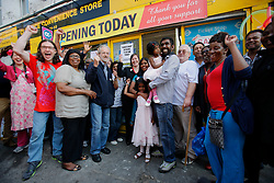 UK ENGLAND LONDON 19AUG11 - Local residents celebrate at the re-opening ceremony of Siva Kandiah's convenience store in Clarence Road, Hackney, east London. Local shopkeeper Siva Kandiah ran the Clarence Convenience Store for 11 years - and had to watch as it was ransacked and destroyed, leaving him with no stock, no money in the till, and no store. During the August riots in London, Clarence Road in Hackney featured some of the most devastating scenes of looting and violence...jre/Photo by Jiri Rezac..© Jiri Rezac 2011