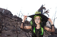 Pretty little witch holding her witch hat and looking away