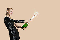 Beautiful young woman uncorking champagne bottle over colored background
