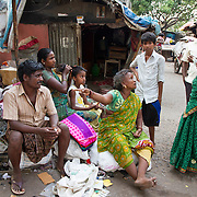 Two women bargain for goods outside their homes in a slum in Chennai, India.