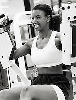 Woman using exercise machine in gym (B&W)