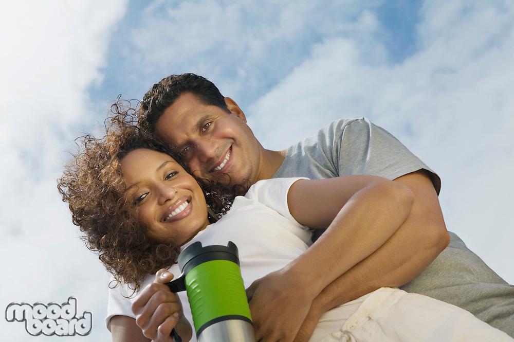 Couple Hugging and Holding Coffee Mug