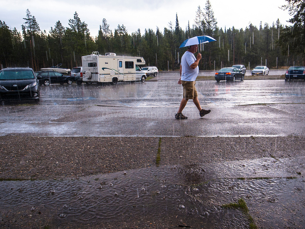 A man shelters from a summer deluge of  rain in Colter Bay, Grand Teton National Park, Wyoming.