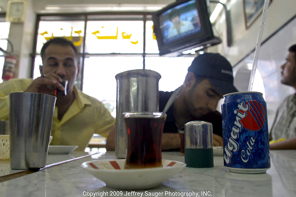 Emad Al-kasid, left, drinks Chai (Iraqi tea) with Maitham Al-Khafiji, center, and Ahmad Al-Hamedi, right, at a restaurant in Damascus, Syria, on Monday, July 14, 2003. Al-kasid and Haider Al-Jubury, members of Iraqi Youth Reunion in Dearborn, MI, have been planning the trip home to Iraq, over the last year. They are visiting their immediate families in Damascus, Syria, as hundreds of thousands of Iraqi Shiite settled in Syria after the Gulf War and their uprising against Saddam Hussein in 1991.Al-Khafiji and Al-Hamedi Haider Al-Jubury's cousin.