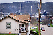 John Fields, 53, sits on the front porch of his family home with the Clairton Coke Works in the background on March 31, 2016.<br /> <br /> Clairton, Pennsylvania, USA, home to the world's largest coke production facility, was founded just after the turn of the 20th century when Crucible Steel Company acquired land along the west side of the Monongahela River 13 miles south of Pittsburgh. <br /> <br /> Struggling for 28 years and designated a distressed municipality by Pennsylvania's Department of Community Affairs, it was finally removed from the distressed classification under the Financially Distressed Municipalities Act (Act 47) in 2015.