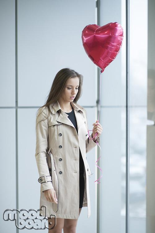 Sad woman holding heart shaped balloon