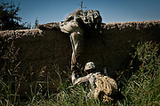 Soldiers climb over a wall on the return to Combat Outpost Nolen.
