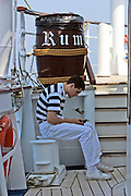 "A rigger phoning home from aboard Royal Clipper. The ""Rum"" barrel is a trash bin."