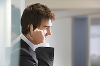 Businessman in doorway talking on cell phone close up side view