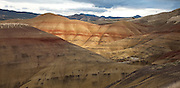 Colorful layers of minerals create bands of color at Painted Hills State park, Oregon. The black soil is lignite that was vegetative matter that grew along the floodplain. The grey coloring is mudstone, siltstone, and shale. The red coloring is laterite soil that formed by floodplain deposits when the area was warm and humid