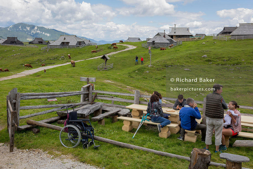Walkers visiting the collection of Slovenian herders' mountain huts in Velika Planina, on 26th June 2018, in Velika Planina, near Kamnik, Slovenia. Velika Planina is a mountain plateau in the Kamnik–Savinja Alps - a 5.8 square kilometres area 1,500 metres (4,900 feet) above sea level. Otherwise known as The Big Pasture Plateau, Velika Planina is a winter skiing destination and hiking route in summer. The herders' huts became popular in the early 1930s as holiday cabins (known as bajtarstvo) but these were were destroyed by the Germans during WW2 and rebuilt right afterwards by Vlasto Kopac in the summer of 1945.