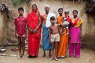"""(L-R) Amit (13), Kelaji Adivasi (45), Tribhuvan Adivasi (50), Akanksha (8), Vinita (23, married when 14, has 3 children), Vinita's baby, and Dharma (18, soon to be married), pose for a family portrait in their house in a tribal hamlet. Tribhuvan, a farm labourer, says that """"it was a mistake to have so many children. Food is difficult for us."""" Kelaji and Tribhuvan have a total of 6 children and live in poverty in Baul ka Dhera hamlet, Mugari Village, Allahabad, Uttar Pradesh, India. Allahabad, a poorer district of the state of Uttar Pradesh, is the most populated district of the most populous state of India. While Ghaziabad, located close to India's capital city, Delhi, has a population of 4,661,452 with a sex ratio of 878 girls against every 1000 boys, and a high literary percentage of 85%, Allahabad, has a population of 5,959,798 and a sex ratio of 902 girls against every 1000 boys and a literacy rate of 74.41%. Photo by Suzanne Lee / Panos London"""
