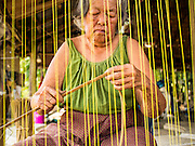 25 APRIL 2014 -  MAE CHAN, CHIANG RAI, THAILAND: An elderly woman weaves papyrus reed matts by hand at her family home in Mae Chan, Chiang Rai province, Thailand. Families in Chiang Rai province still make woven reed matts by hand. The matts are used around the house as an impromptu table, and farmers as something to spread out on the ground during lunch, like a picnic blanket. They cost anywhere from 15Baht (.50¢ US) to 150Baht ($5.00 US) depending on size.    PHOTO BY JACK KURTZ
