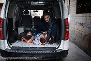 SYRIA, HOMS, Baba Amro: A Syrians man hold the head of a seriously wounded man as he arrive in front of the entrance of a house used as hospital in Baba Amro, southern neighborhood of Homs on February 06, 2012.  ALESSIO ROMENZI