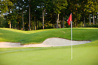 groomed golf hole with green grass, raked sand trap and red flag