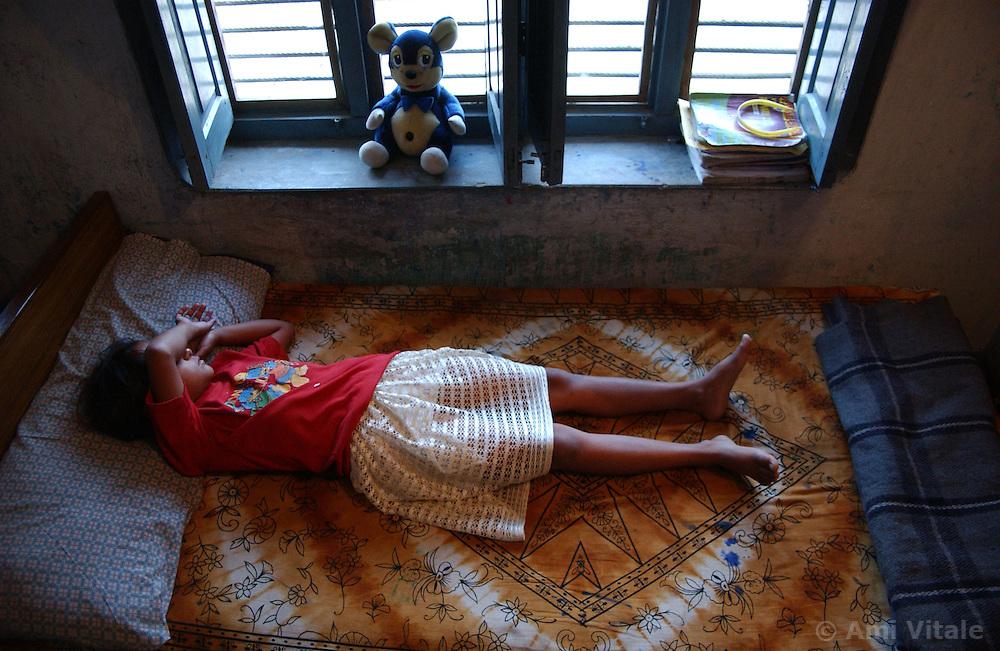 NEPALGANJ, NEPAL, APRIL 15, 2004: A Nepali girl who was orphaned because of the Maoist insurgency sleeps inside the Sahara orphanage in Nepalganj, Nepal April 15, 2004.   (Ami Vitale/Getty Images)