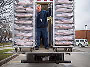 """26 MARCH 2020 - DES MOINES, IOWA: A school district worker unloads hot lunches at Weeks Middle School. Des Moines Public Schools (DMPS) started distributing hot lunches Thursday, the first day students were supposed to return to school. Schools will now remain closed until 13 April. Meals were distributed with """"social distancing"""" in mind. On Thursday morning, 24 March, Iowa reported 175 confirmed cases of the Coronavirus (SARS-CoV-2) and COVID-19. Restaurants, bars, movie theaters, places that draw crowds are closed until 07 April. The Governor has not ordered """"shelter in place""""  but several Mayors, including the Mayor of Des Moines, have asked residents to stay in their homes for all but the essential needs. People are being encouraged to practice """"social distancing"""" and many businesses are requiring or encouraging employees to telecommute.         PHOTO BY JACK KURTZ"""