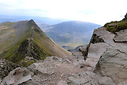 Descending the steep summit cliffs of Helvellyn onto the famous Striding Edge arete. St.Sunday Crag is seen in the distance across Grisedale.<br />