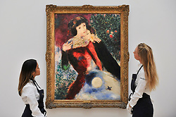 "© Licensed to London News Pictures. 06/10/2017. London, UK. A staff members view ""Les Amoureux"", 1928, by Marc Chagall at a preview at Sotheby's in New Bond Street of contemporary, impressionist and modern art works to be auctioned in New York in November 2017 Photo credit : Stephen Chung/LNP"