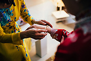 A mother puts a bracelet on the bride-to-be at a Chinese wedding. Ko Samui, Thailand, Southeast Asia