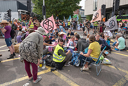 © Licensed to London News Pictures. 17/07/2019; Bristol, UK. Extinction Rebellion Summer Uprising 2019. Police remove protesters arresting some and putting them in police vans as they try to clear a major road junction occupied by an Extinction Rebellion protest which has caused major traffic disruption. Campaigners locked themselves onto a pink bath tub, and held 7 minute roadblocks on other parts of the junction complex. Extinction Rebellion are holding a five-day 'occupation' of Bristol, by occupying Bristol Bridge in the city centre and traffic has to be diverted and carrying out other events. As part of a country-wide rebellion called Summer Uprising, followers will be holding protests in five cities across the UK including Bristol on the theme of water and rising sea levels, which is the group's focus for the South West. The campaign wants the Government to change its recently-set target for zero carbon emissions from 2050 to 2025. Photo credit: Simon Chapman/LNP.