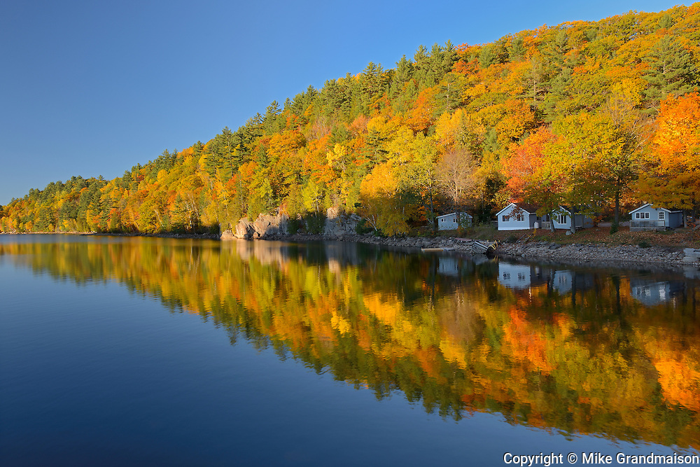 Hiilside of autumn colored trees reflected in Lake St. Nora<br /> Near Pine Springs<br /> Ontario<br /> Canada