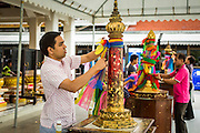 05 MAY 2013 - BANGKOK, THAILAND:  Thais tie colored silks to posts at the City Pillar Shrine as a part of prayers. The silks signify that spirits live in the shrine. The City Pillar Shrine was the first building built in Bangkok, on April 21, 1782, when then King Rama I moved the capital of Siam (now Thailand) from Thonburi to its present location in Bangkok. The shrine is called Lak Mueang in Thai is revered by the residents of Bangkok.      PHOTO BY JACK KURTZ