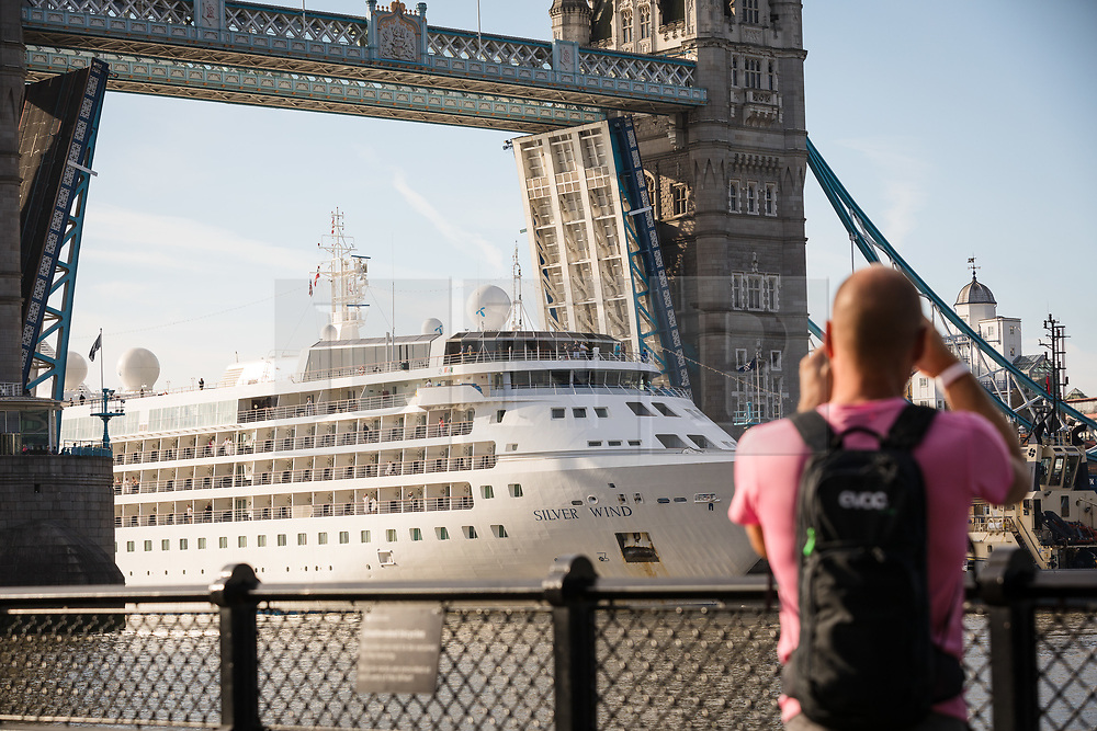 © Licensed to London News Pictures. 01/08/2017. LONDON, UK.  A man photographs Silver Wind, a huge 514 feet long, 17,400 ton cruise liner as she leaves London under Tower Bridge this morning after a brief visit, towed backwards by two tugs. Silver Wind carries just 296 passengers and its owner, Silversea claim that the ship has amongst the highest space-to-guest ratios in the cruise ship industry, with the largest suites measuring 1,314 square feet. Tickets cost thousands of pounds, but all guest expenses, even champagne are included in the price. Environmentalists claim the pollution created by giant cruise ships outweigh their economic benefits. The Port of London Authority (PLA) are conducting a work programme during 2017 to monitor air quality and pollution caused by river traffic on the River Thames.  Photo credit: Vickie Flores/LNP
