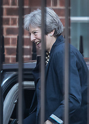 © Licensed to London News Pictures. 22/10/2018. London, UK. Prime Minister Theresa May smiles at her close protection officer as she arrives at the back entrance to Downing Street. Mrs May is coming under increasing pressure over the progress of Brexit negotiations. Photo credit: Peter Macdiarmid/LNP