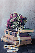 a dried rose bouquet on a pile of old books