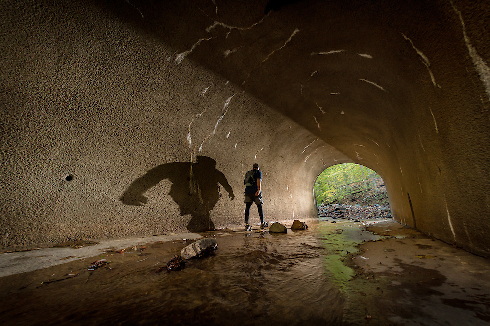 A lone runner crosses under railroad tracks via a tunnel during the Patapsco 50k Ultramarathon.
