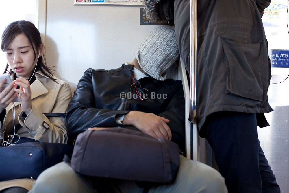 man trying to sleep in the train by pulling a knitted hat over his head Tokyo Japan